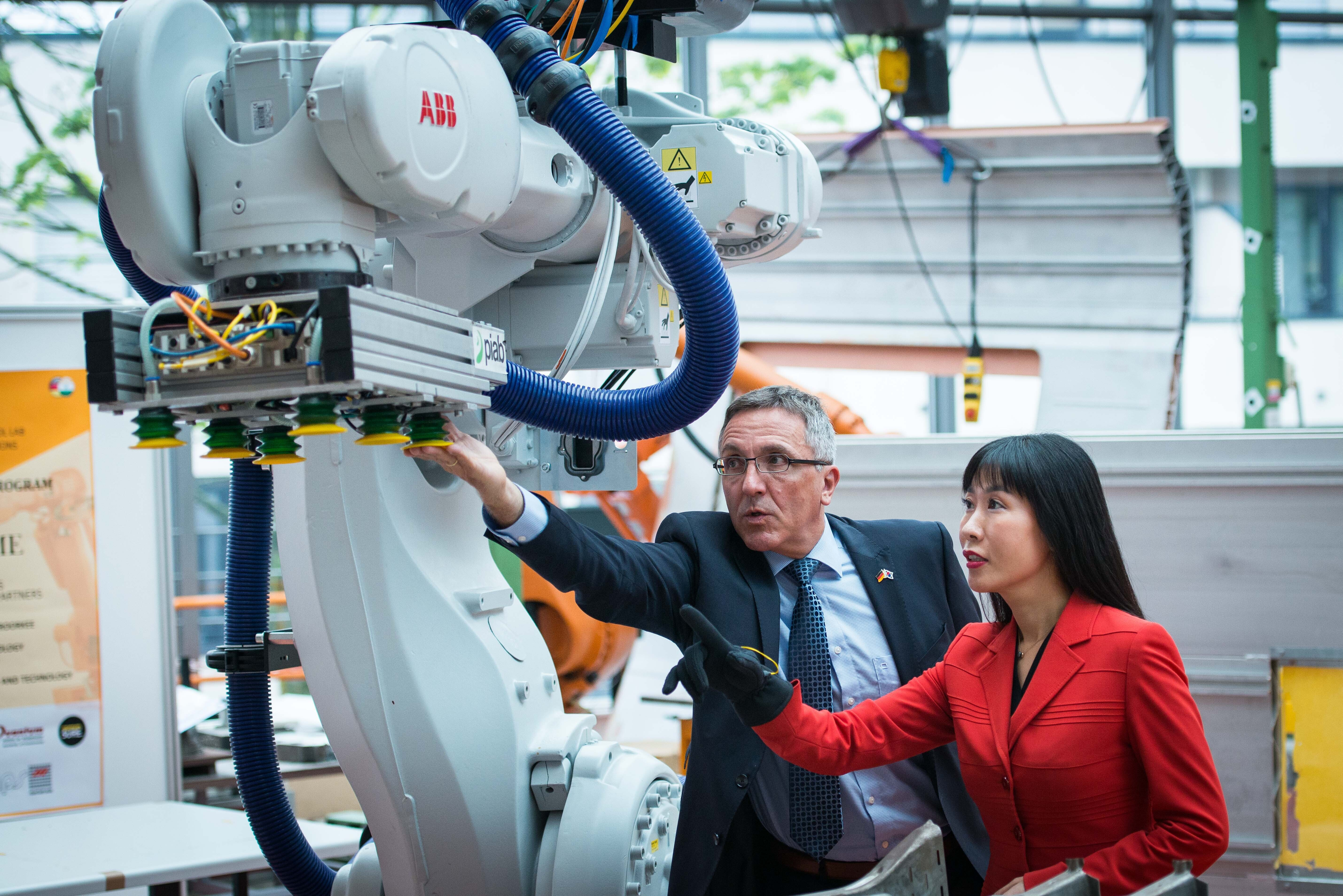 Professor Dr Thomas Gries and Soyeon Schröder-Kim with data glove at the industrial robot
